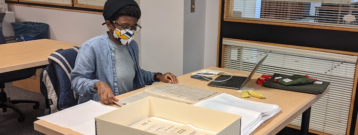 Dr. Kianna Middleton sits at a table in the Morgan Library Reading Room. She is reviewing print materials from the CSU Libraries' Friedman Feminist Press Collection.
